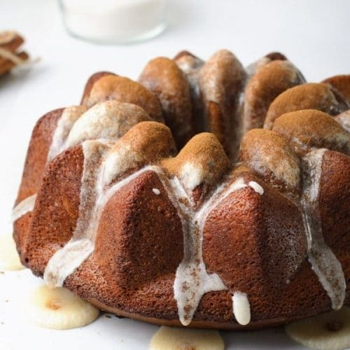 a dark brown bundt cake with ribbons of white glaze dripping down the crevices and a light dusting of cinnamon on top