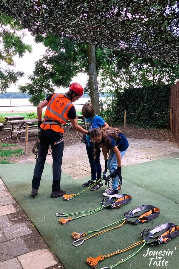 a man in an orange vest and red helmet checks the harness on a boy as a girl puts on her own harness