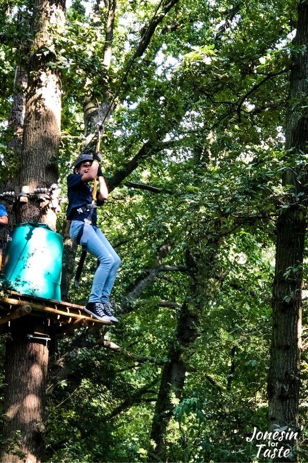 a girl rides a zipline through the trees