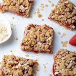 5 squares of strawberry bars sitting on a white background with crumbs and fresh strawberries artfully arranged around them