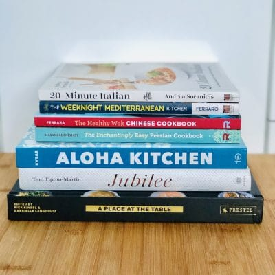 a picture of a colorful stack of cookbooks with text that says our family's favorite global cuisine cookbooks
