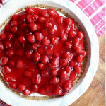 cherry pie filling is haphazardly spread on a creamy white pie with a graham cracker crust sitting in a round white pie pan