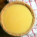 a golden yellow vanilla pie with a light golden brown crust sitting on a red and white tea towel