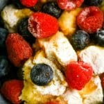 a close up view of bread pudding topped with blueberries and raspberries and a light dusting of powdered sugar