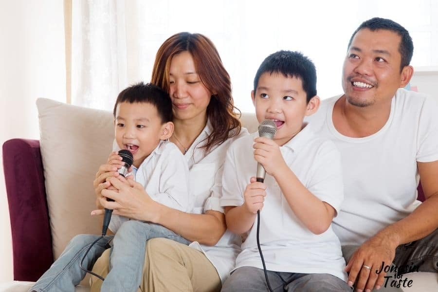 an Asian family with a mother father and 2 young sons sits together on a couch singing karaoke.