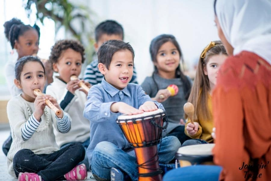 a small group of young children of various ethnicities sit on the floor playing different instruments. We can see the back of their female teacher who is wearing a hijab