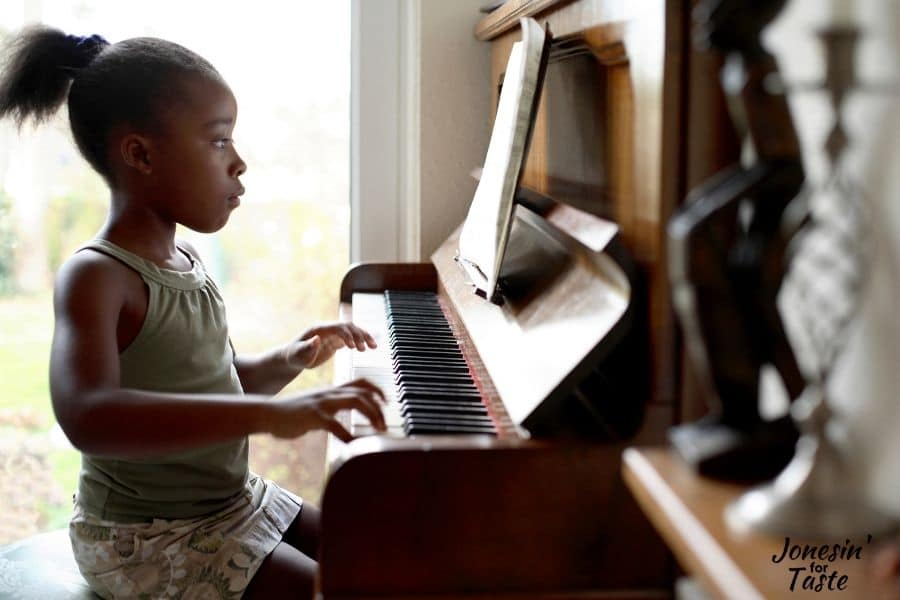 a dark skinned black girl sits at a piano playing studiously