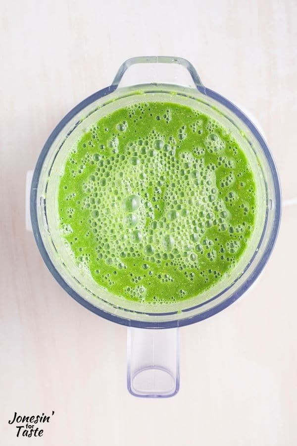 looking down into the blender cup full of a bright green liquid with bunches of bubbles on top