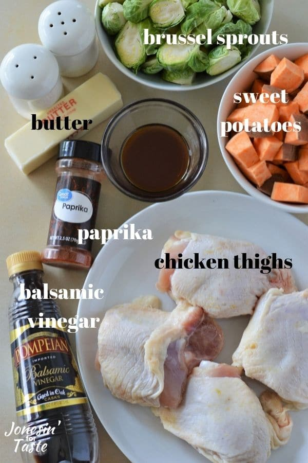 salt and pepper shakers, bowls of maple syrup, brussels sprouts and sweet potatoes, a plate of chicken thighs, and bottles of Balsamic vinegar and paprika on a table