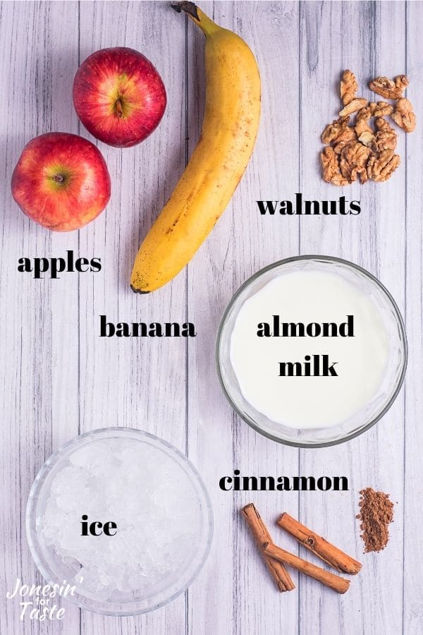 apples, a banana, a small handful of walnuts, almond milk and ice in bowls, and cinnamon sticks with a little pile of ground cinnamon sit on a light wooden background