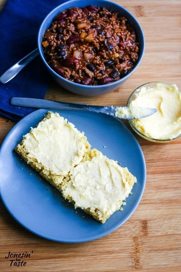 a halved square of cornbread spread with honey butter sits on a blue plate next to a bowl of chili and a small bowl of honey butter