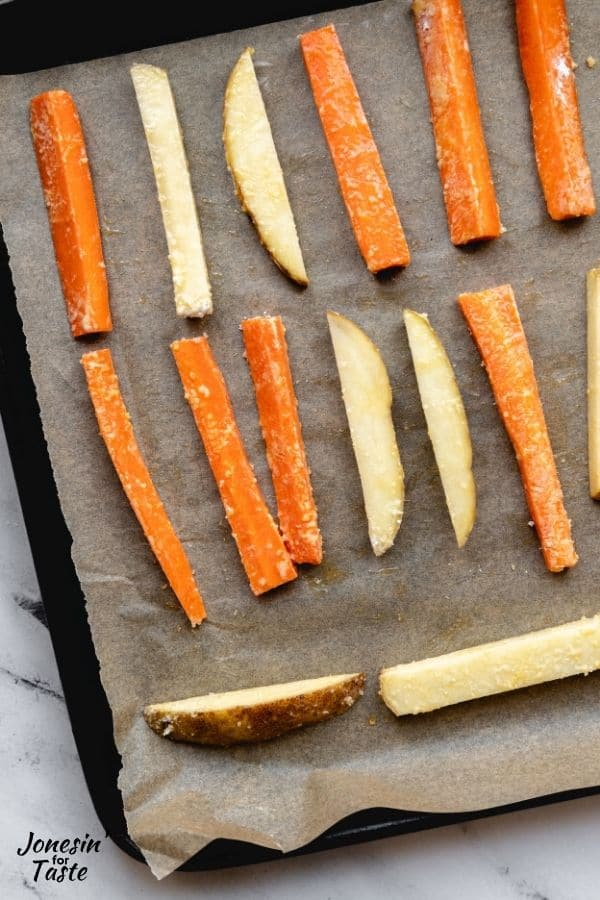uncooked carrot and potato fries in rows on a piece of parchment paper