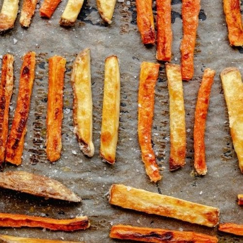 baked carrot and potato fries mixed together in rows on a cookie sheet