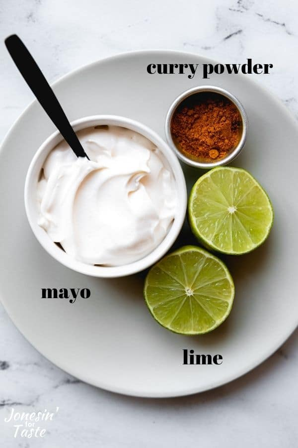 a halved lime and bowls of mayo and curry powder on a small grey plate