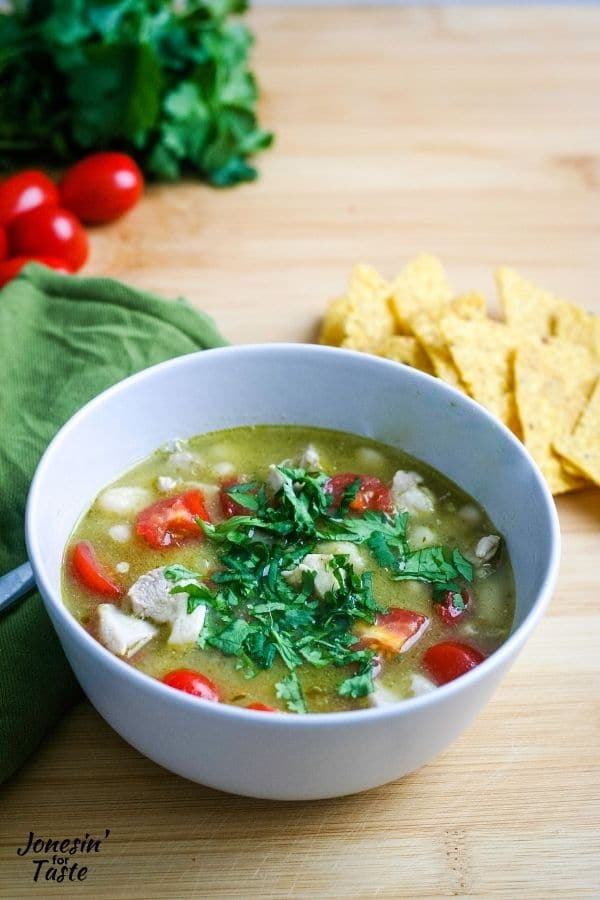 a bowl of green chicken chili on a wooden backdrop surrounded by chips, a green napkin, cherry tomatoes, and a bunch of cilantro