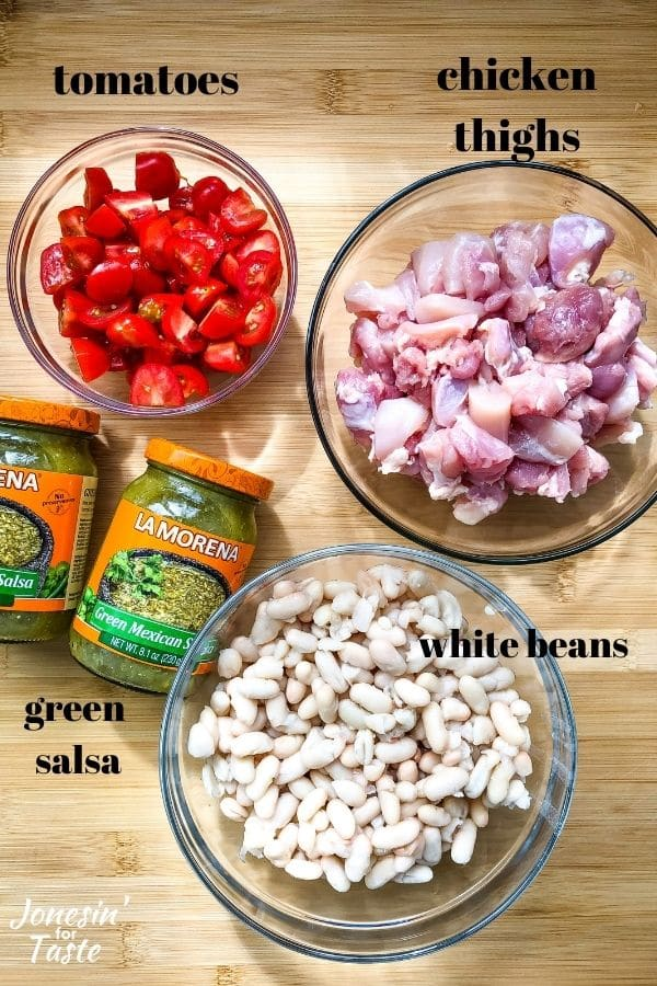 glass bowls of halved cherry tomatoes, diced chicken thighs, and rinsed white beans next to 2 jars of salsa verdeon a wooden cutting board