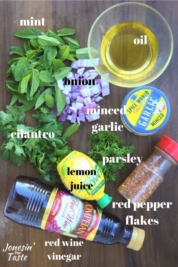 mint, parsley, chopped red onion, a cup of olive oil, a jar of minced garlic, parsley, and bottles of red pepper flakes, red wine vinegar, and lemon juice