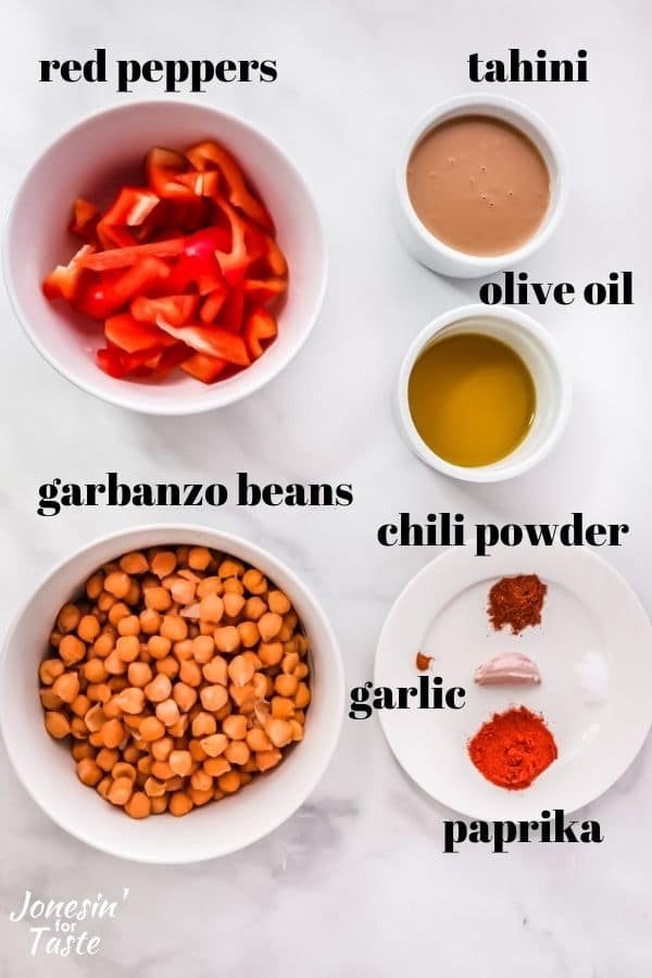 white bowls with chopped red peppers, tahini, olive oil, and garbanzo beans alongside a plate with chili powder, garlic, and paprika.