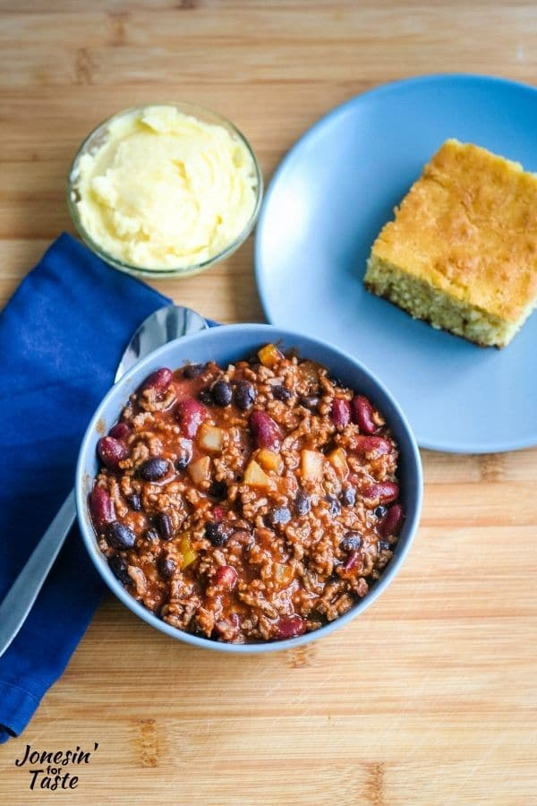 a bowl full of beef and bean chili next to a plate of cornbread and small bowl of honey butter