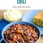 a bowl full of beef and bean chili next to a plate of cornbread and small bowl of honey butter. Text above the photo says slow cooker chili easy fall favorite