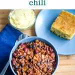 a bowl full of beef and bean chili next to a plate of cornbread and small bowl of honey butter. Text above the photo says easy weeknight dinner slow cooker chili