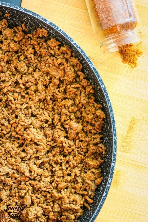 a jar of spices tipped over next to a pan of taco meat