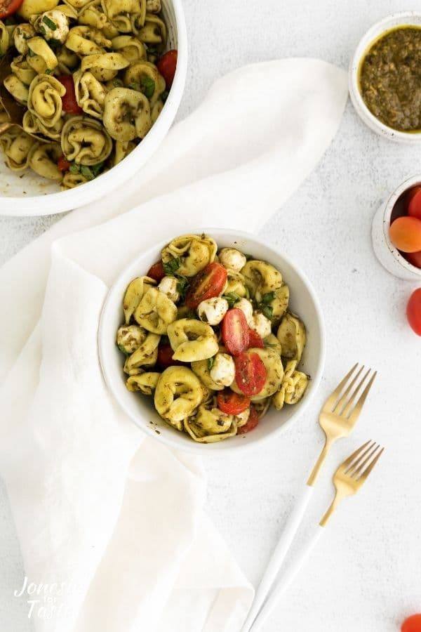 a portion of tortellini pasta salad in a white bowl surrounded by a white linen napkin, white handled forks, and other various bowls with the pasta salad and various ingredients.