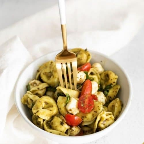 a hand holding a fork. The fork is pressing down on a tortellini in a white bowl to pick up.